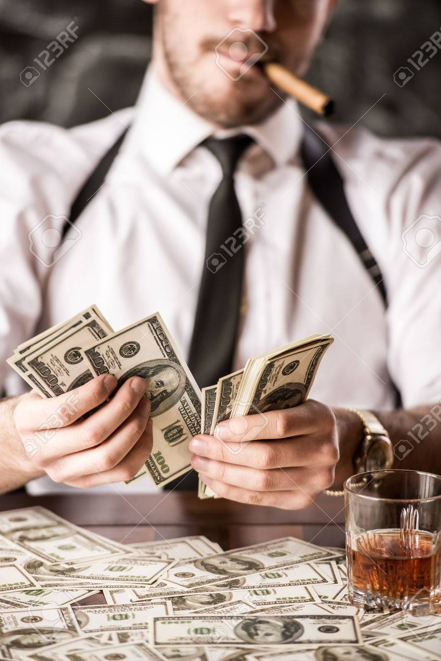 36818231-gangster-in-shirt-and-suspenders-is-counting-money-and-smoking-cuban-cigar-while-sitt...jpg